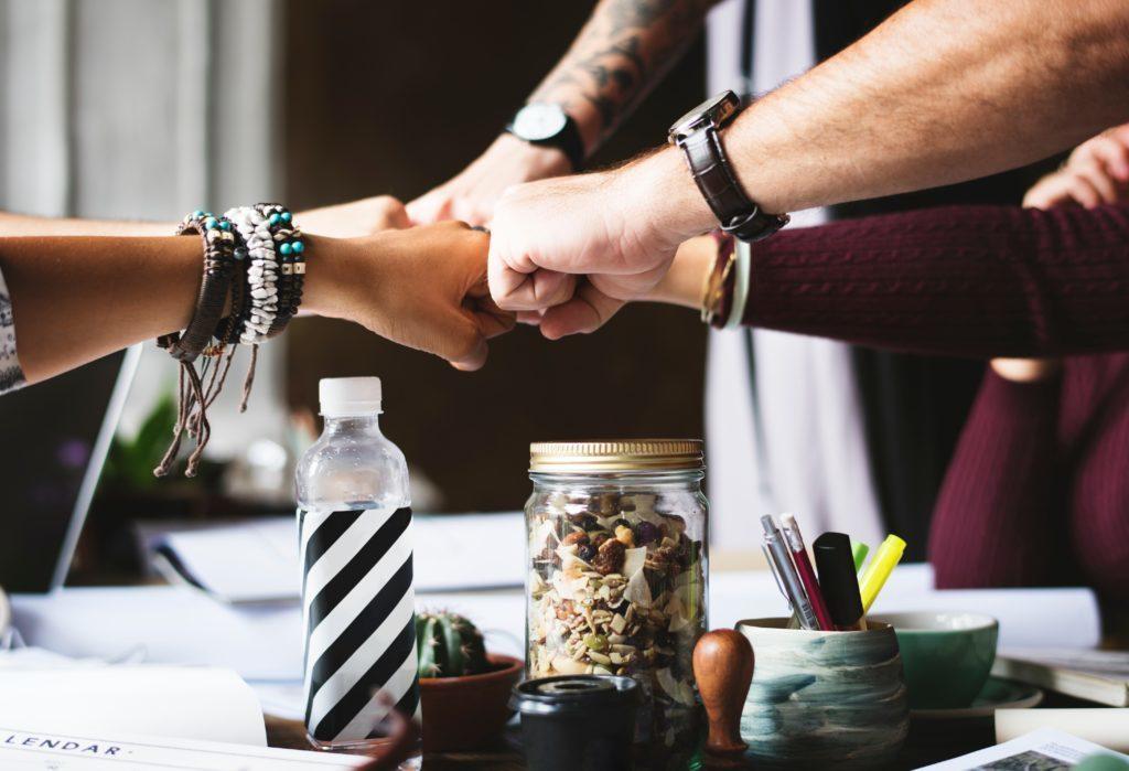 Kooperation: Menschen halten Fäuste zusammen und bilden einen Stern
